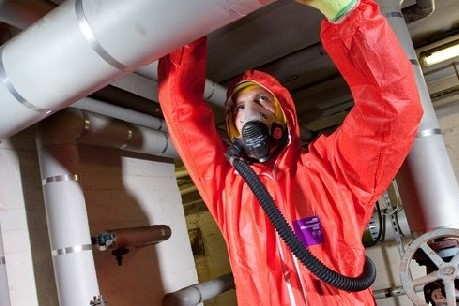 A man in PPE reaching up to a pipe.