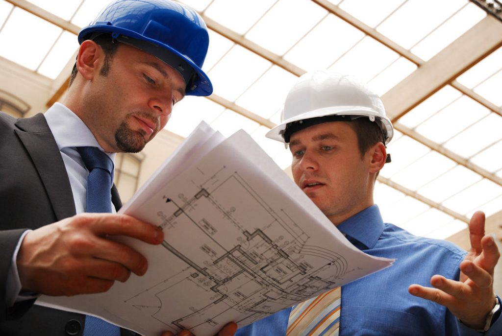 Two men in suits and hard hats looking at building plans.