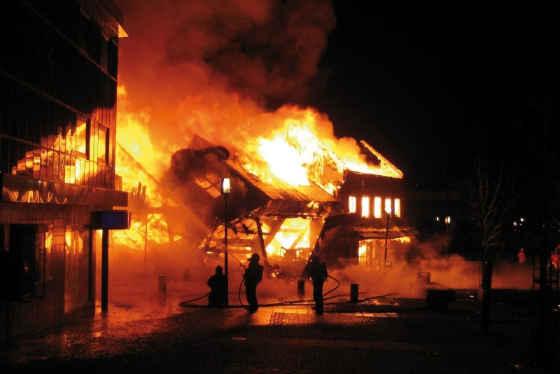 A building on fire as two fire fighters use a hose.