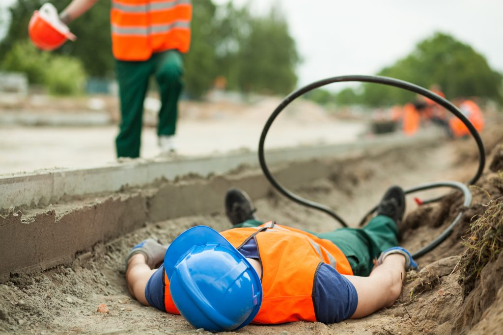 A construction worker lies on the ground as a colleague rushes to help him.