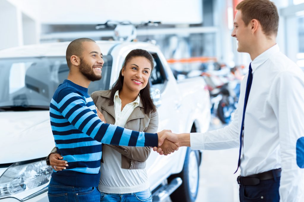 Man in shirt shaking hands with a man and women