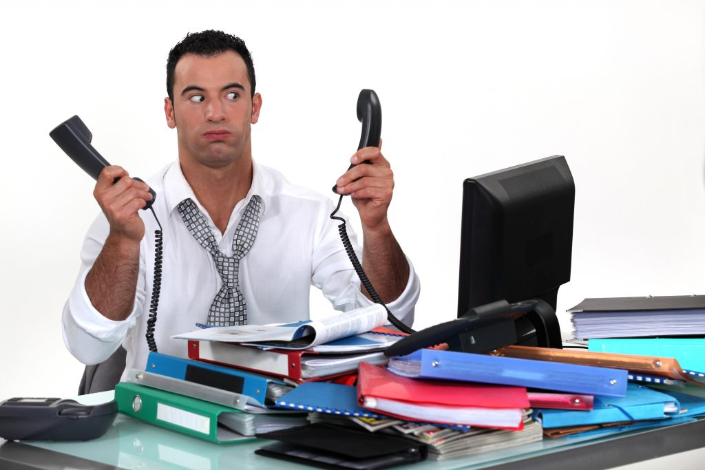 Man holding too phones with lots of work around him
