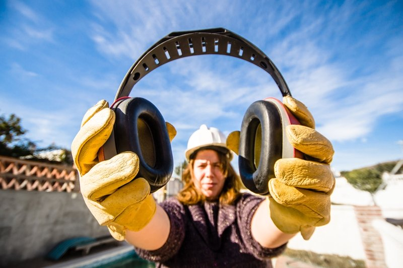 Female construction worker holding noise cancelling headphones
