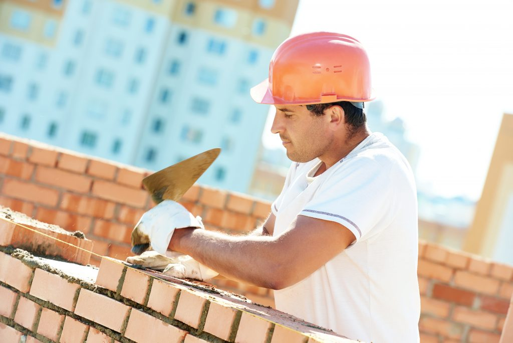 Bricklayer laying down some bricks on a wall