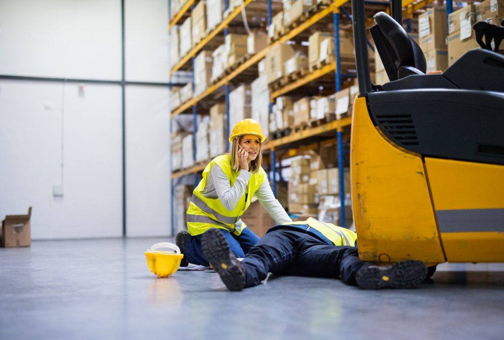 A female worker in a high vis vest and hard hat on the phone kneeling next to a man who has fallen on the ground.