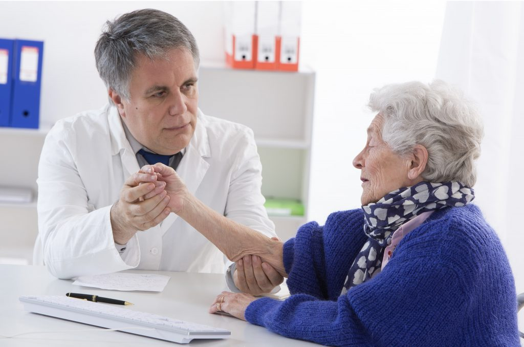 A male doctor holding the hand of an elderly woman.