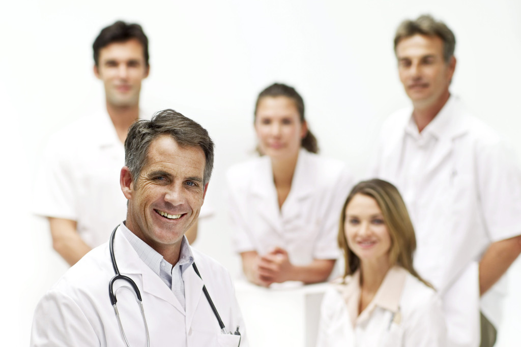 A male doctor smiling in front of some colleagues.