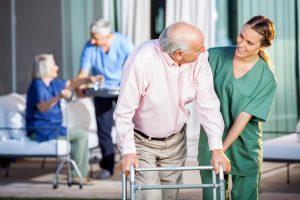 A female nurse guides an elderly man using a Zimmer frame.