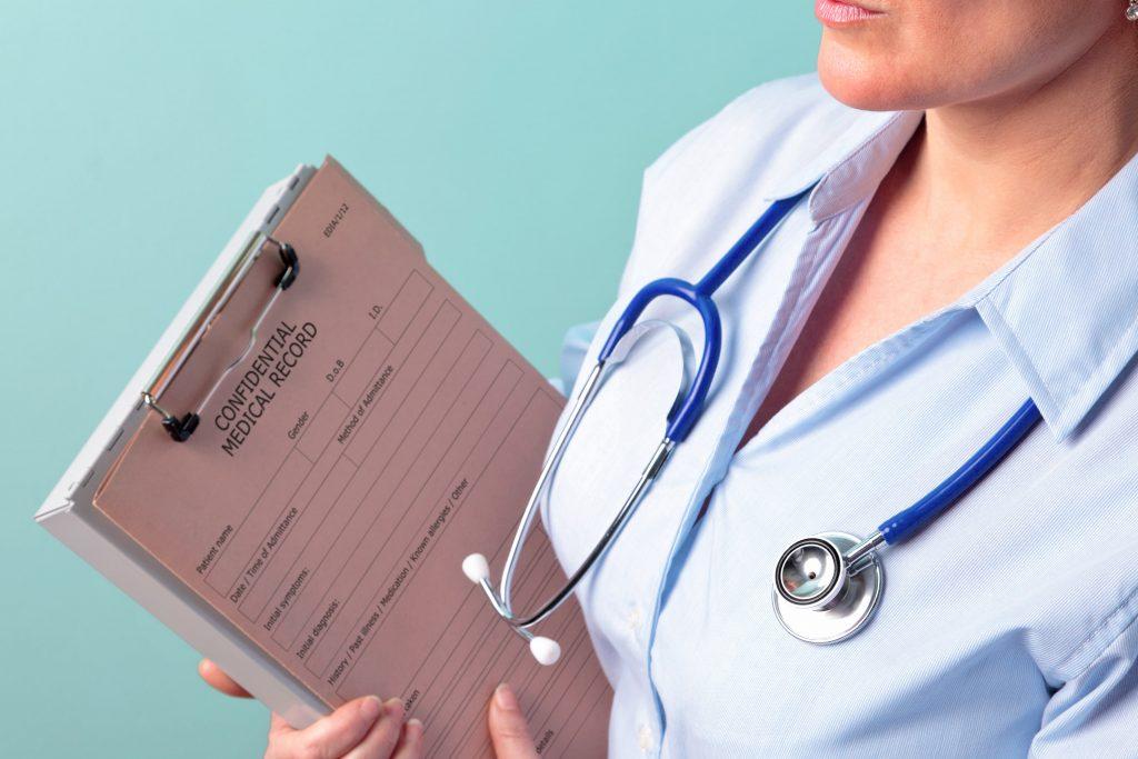 A female nurse holding a confidential medical record.