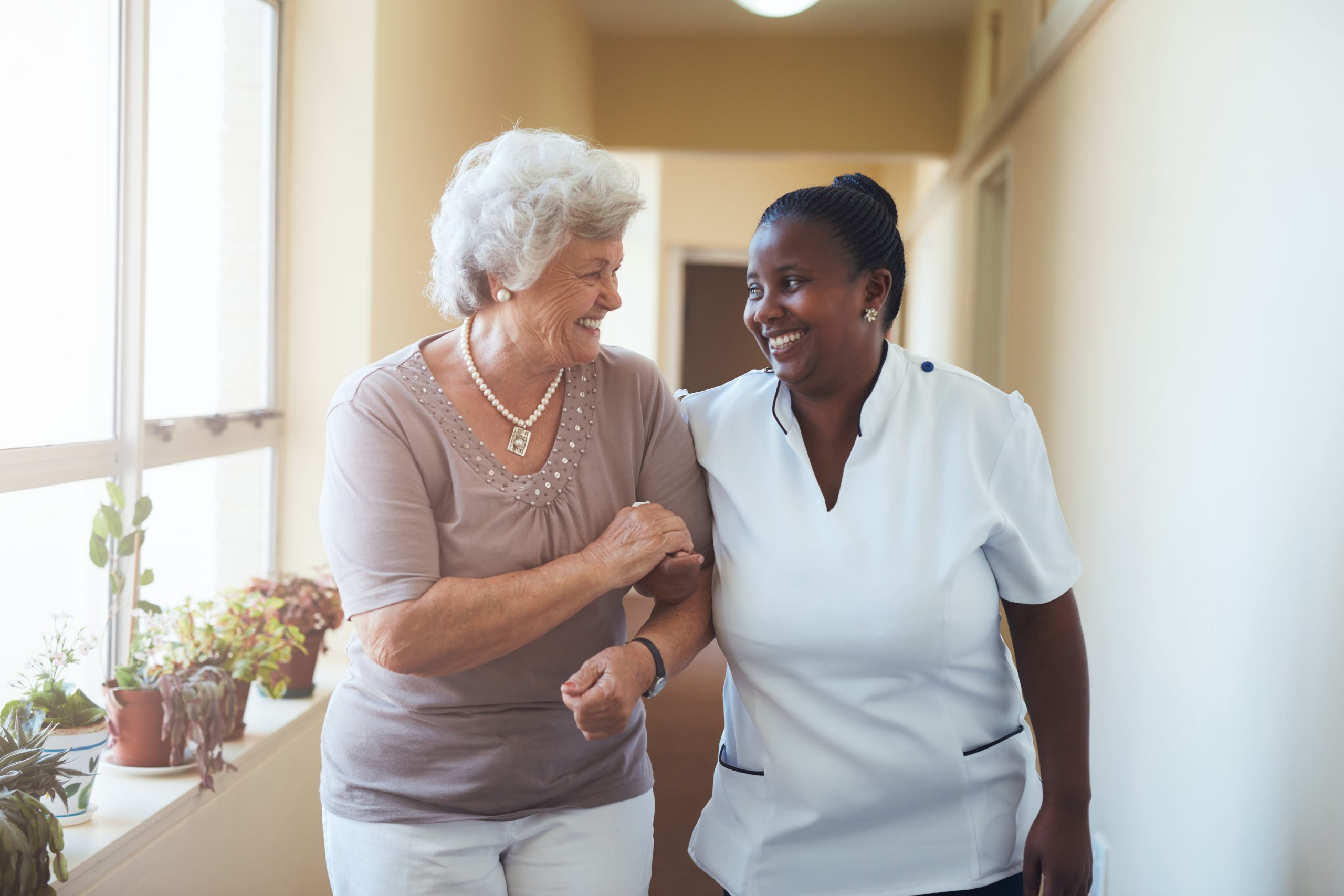 A female cure worker linking arms and smiling with an elderly woman.
