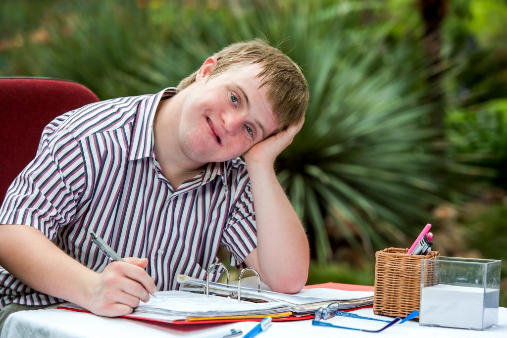 A man with learning disabilities sat at a table with a pen and a folder of work.