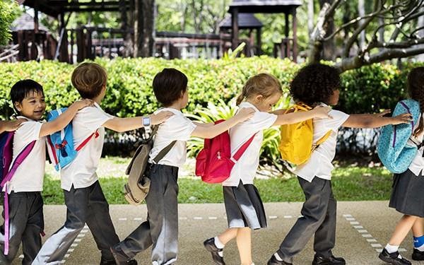 Pre-school children walking together in a line.