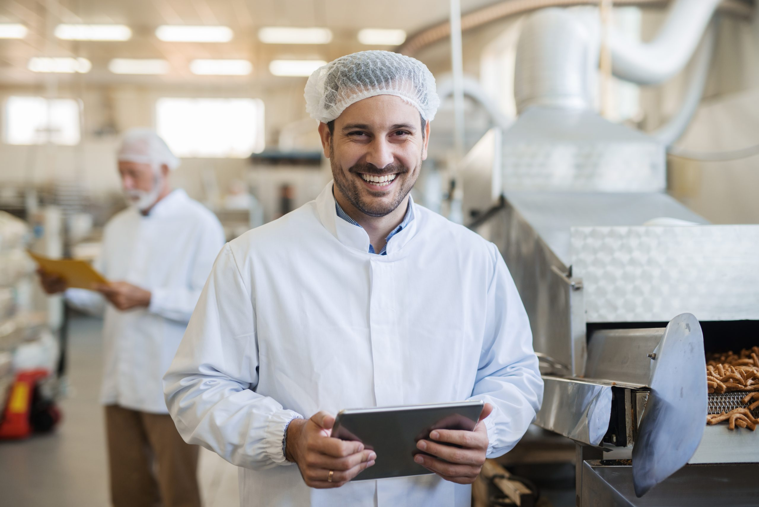 A man in a professional kitchen wearing white overalls and a hair net smiling holding a tablet computer.
