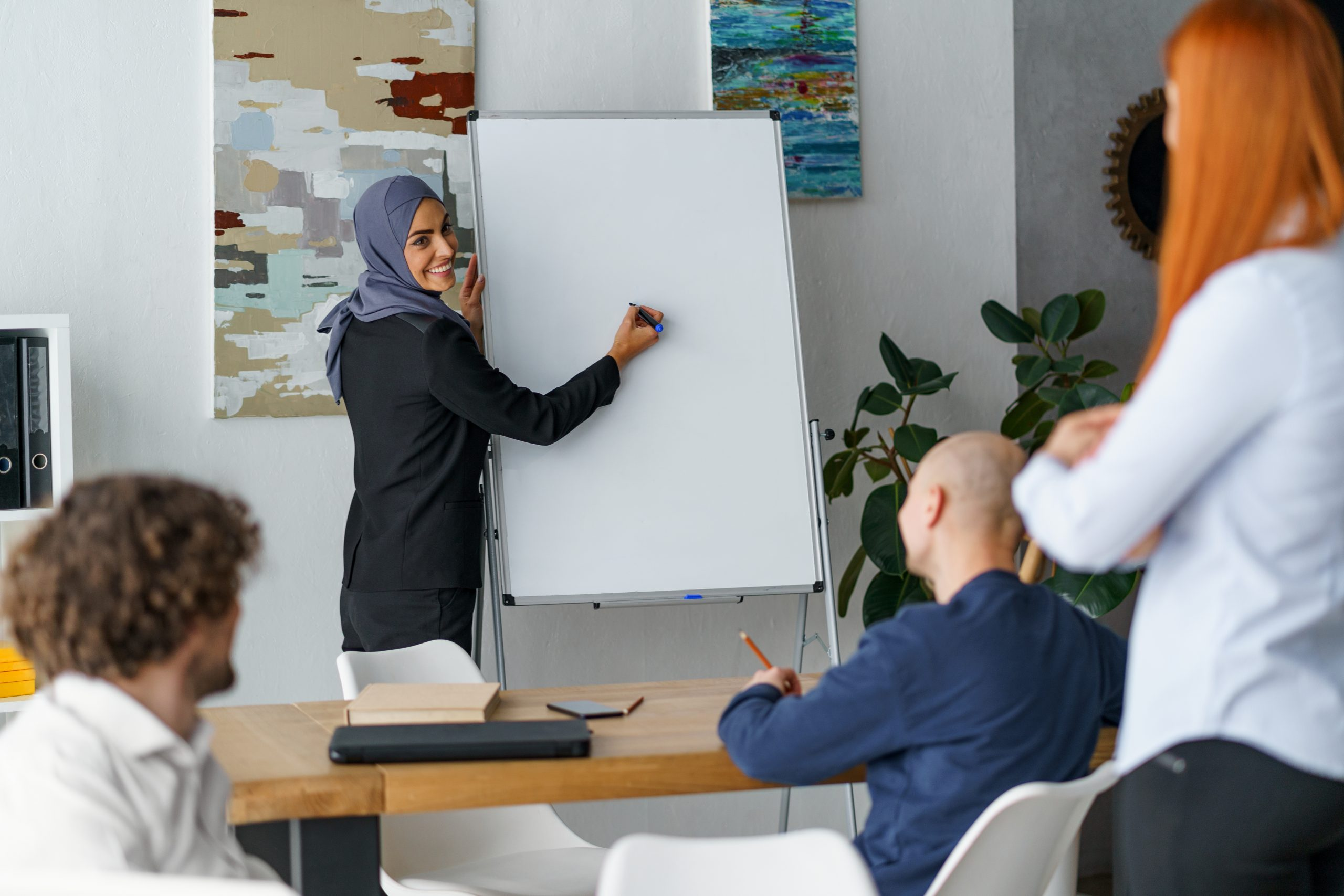 A woman writing on a whiteboard and delivering some training.