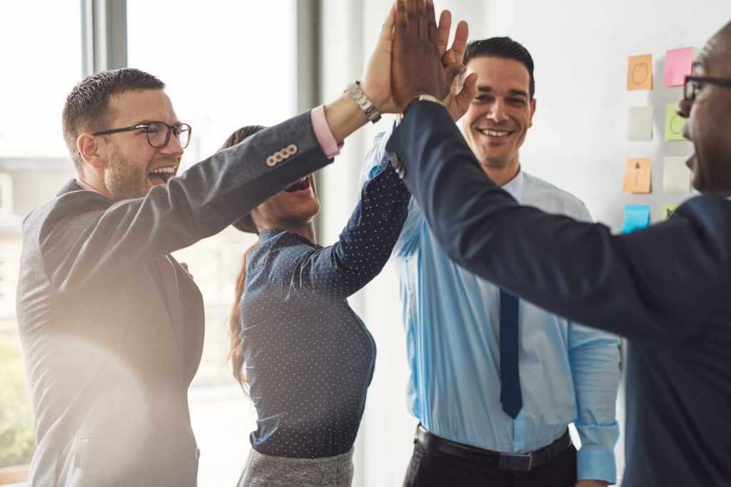 A group of colleagues doing a high five.
