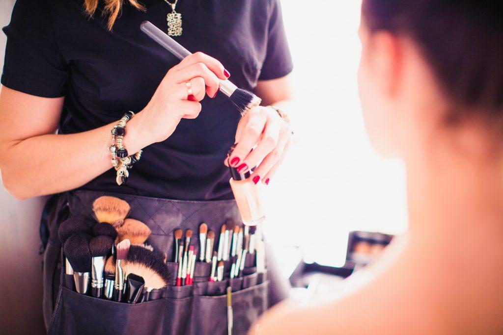 A makeup artist holding a brush.