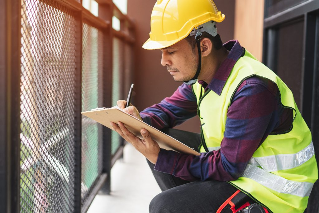 Construction worker writing something down on notepad