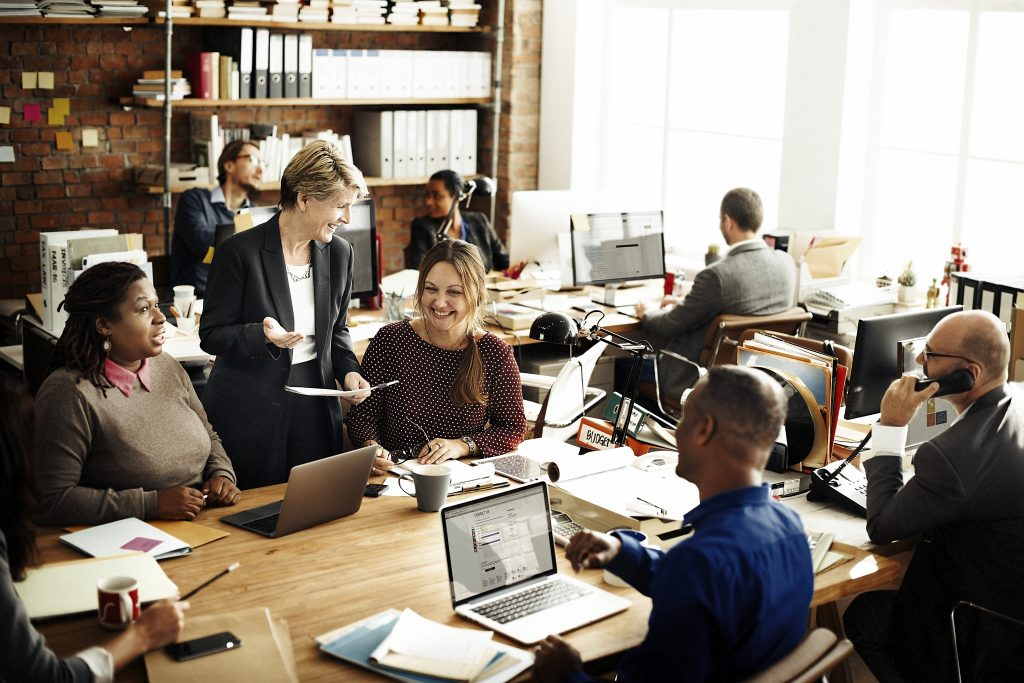 Picture of a busy office with people working around a table
