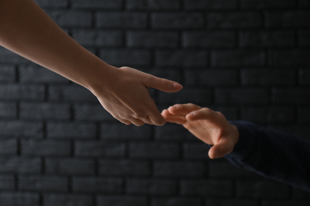Two hands reaching out towards each other
