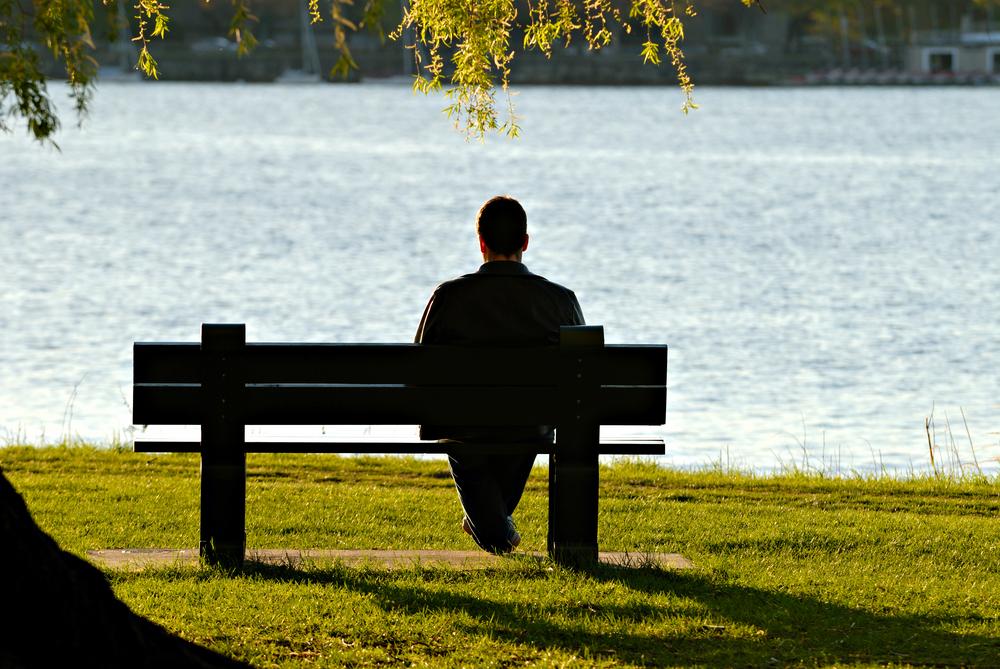 Man sat on bench facing lake