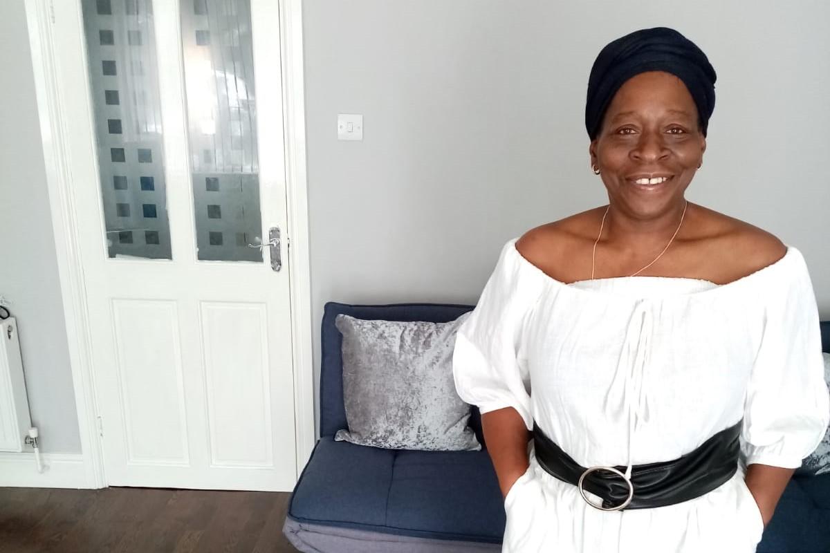 Black female standing inside wearing a white dress