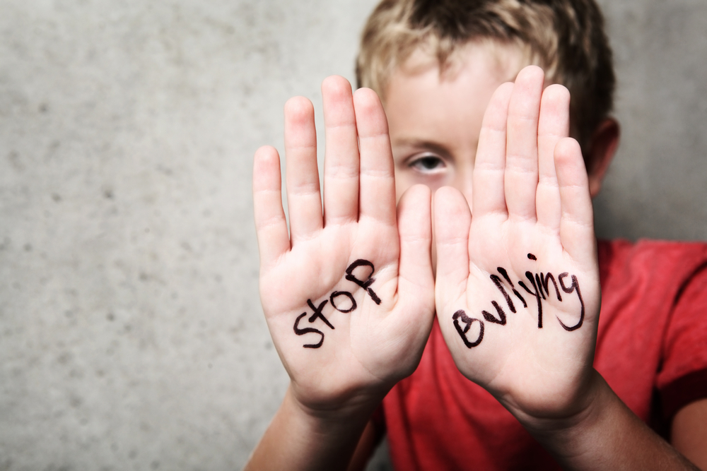 A young boy holding up his hands with stop bullying written on them