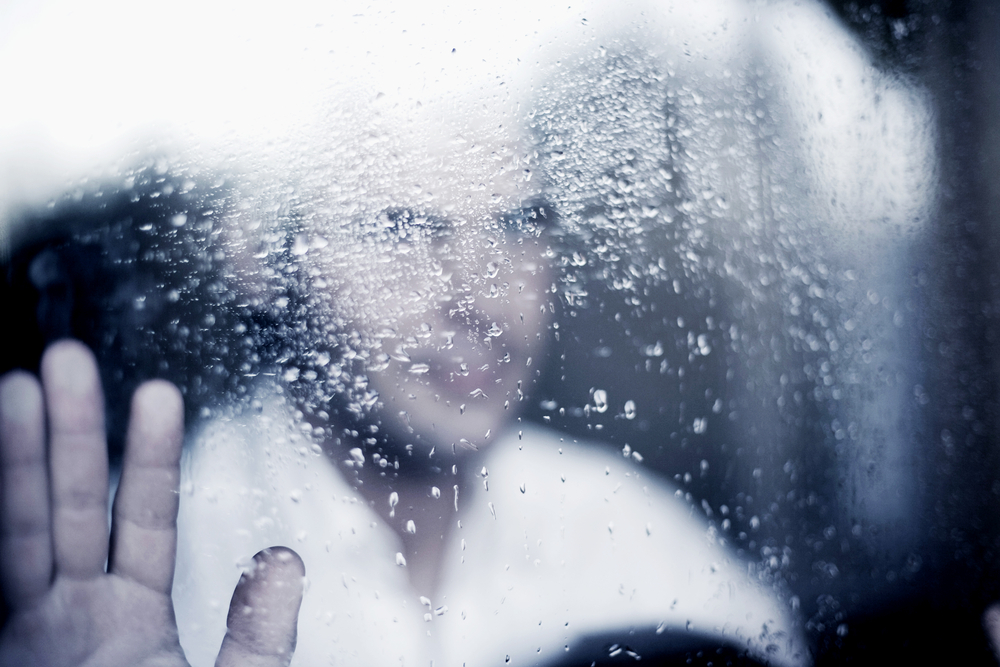 Man staring through window looking out with hand on glass