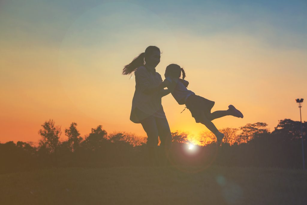 Sunset with woman holding child