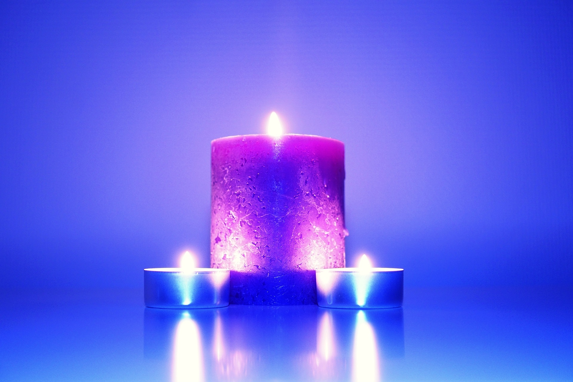 Pink candle burning in front of a purple background