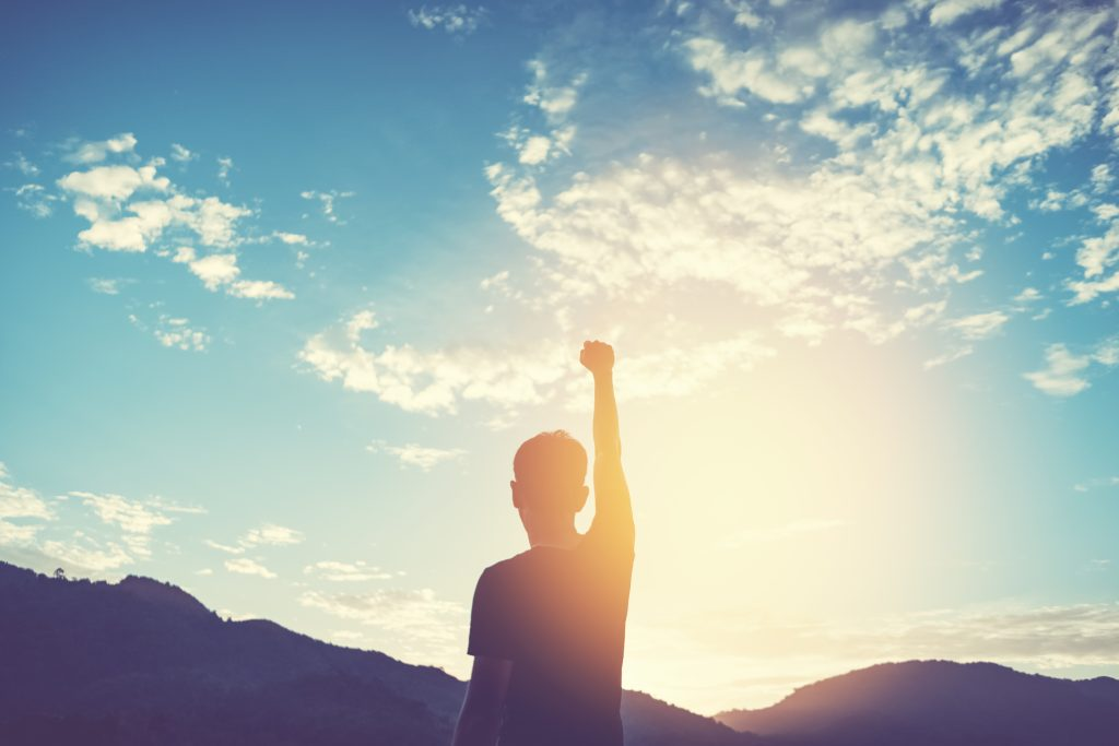 Man with fist in the air whilst watching sunrise
