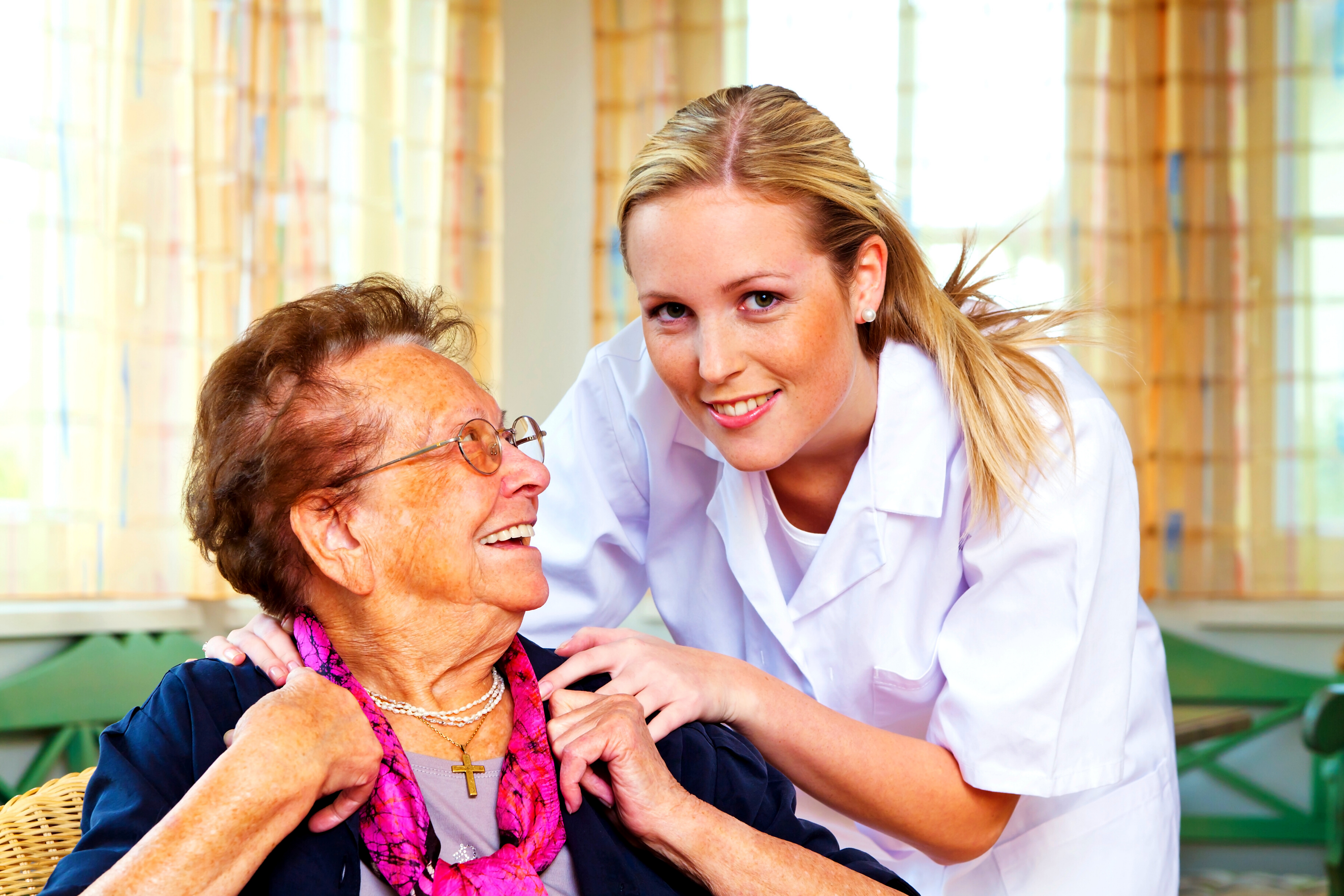 A female care worker with an elderly lady smiling up at her