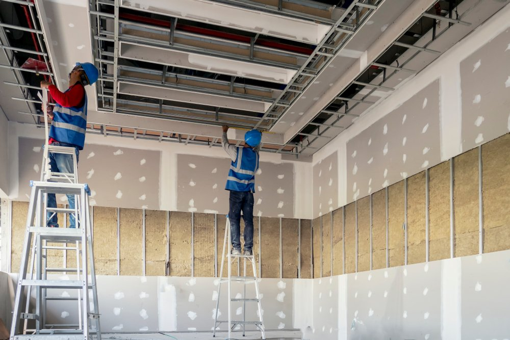 Two construction workers working on a ceiling