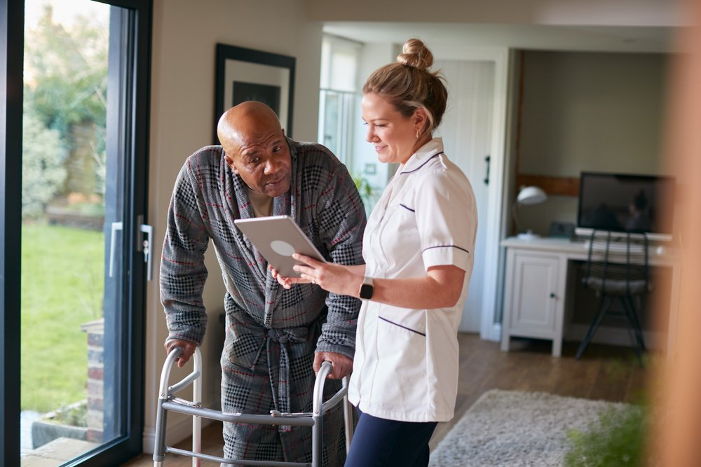Health care assistant witha tablet talking to an elderly man