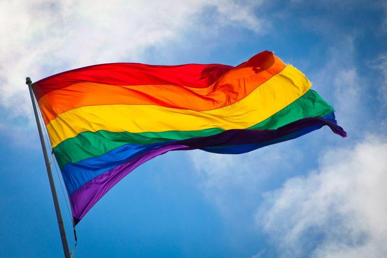 Rainbow Pride flag flying against a blue sky