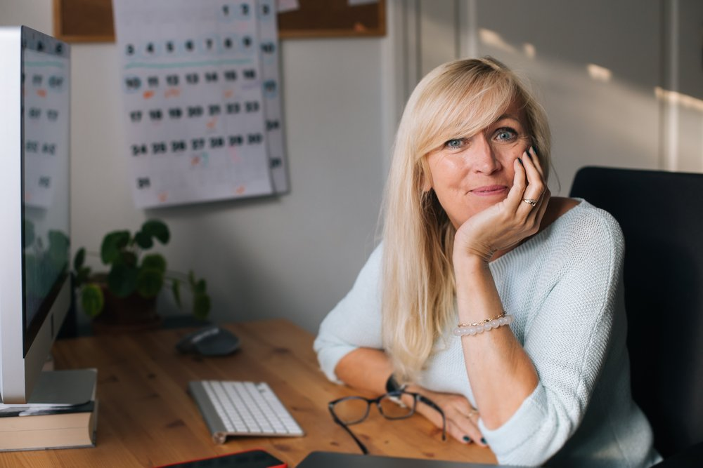 Portrait of smiling mature woman working on computer in her home office.