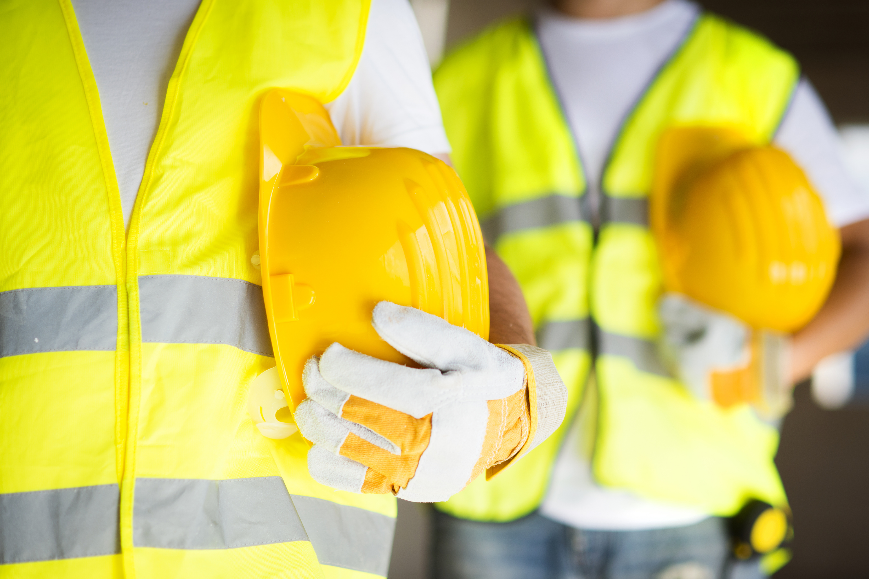 Photo of two construction workers wearing high vis vests holding hard hats