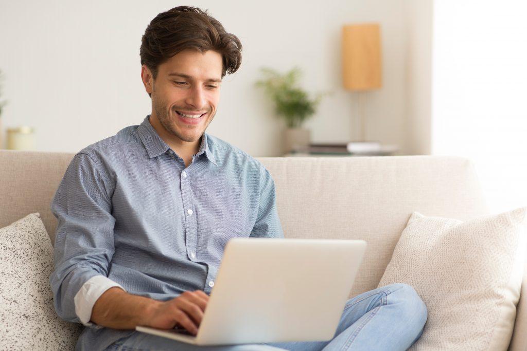 Man with laptop sat on sofa smiling
