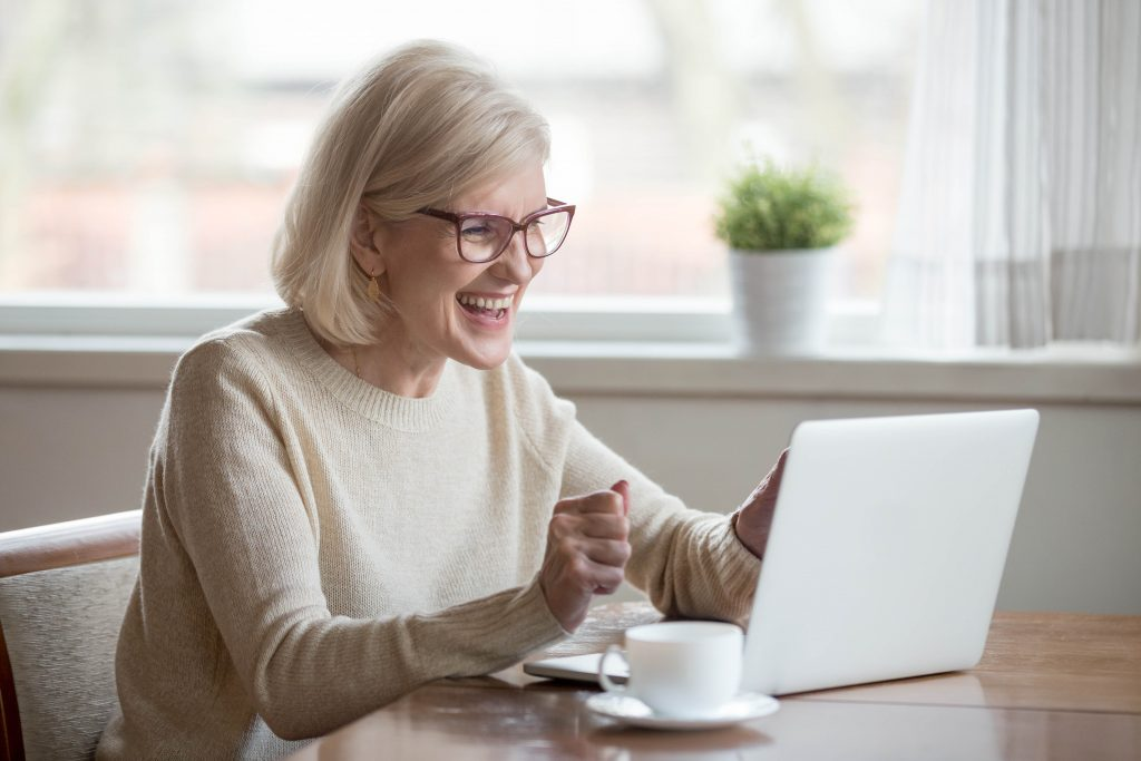 Mature woman using laptop at dek