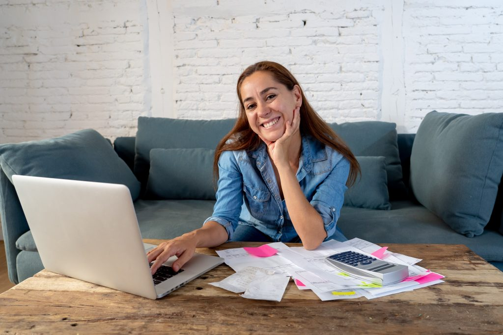 Woman smiling touching laptop with bank statements on desk with calculator