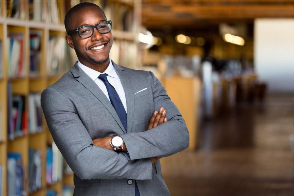 Smartly dressed man stood in a library