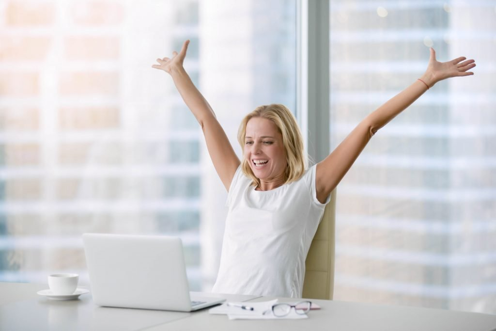 Woman celebrating with laptop on desk